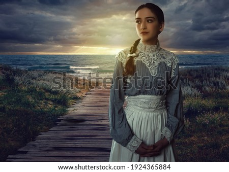 Young victorian girl in white dress and blue striped blouse on the coast at sunset. Сток-фото ©
