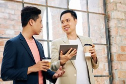 Young Vietnamese coworkers drinking take away coffee and discussing information on dgital tablet