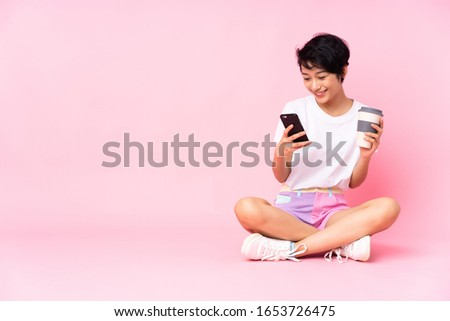 Young Vietnamese woman with short hair sitting on the floor over isolated pink background holding coffee to take away and a mobile