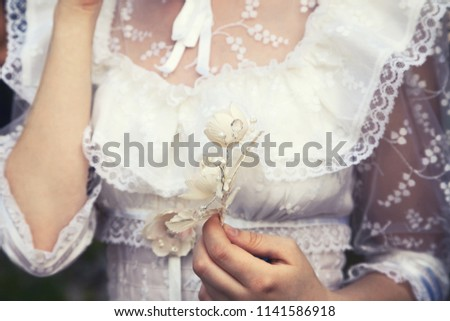 Young virgin girl in a white lace wedding dress holding a flower. Tender delicate woman at a wedding  #1141586918