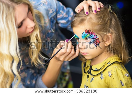 Young visagist painting the face of a little girl #386323180