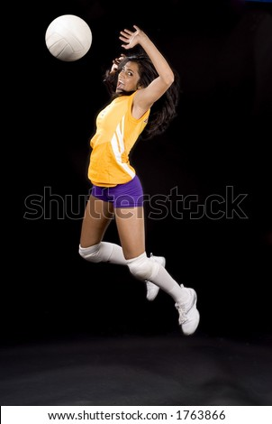 young volleyball girl in mid spike pose