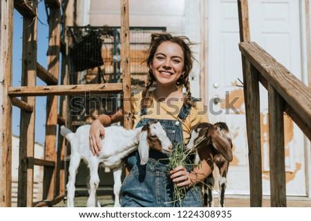 Young volunteer feeding baby goats