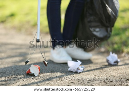 Young volunteer picking up litter in park, closeup