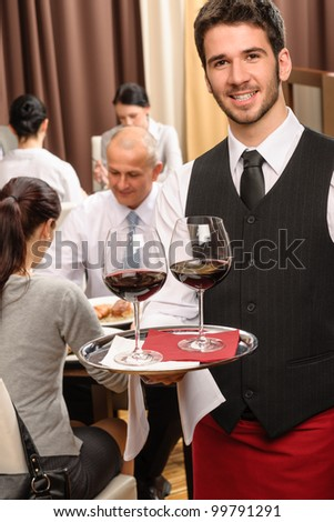 Young waiter hold red wine business lunch at professional restaurant