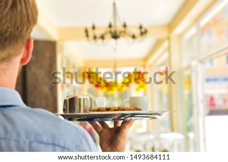 Young waiter serving coffee and cookies at restaurant #1493684111