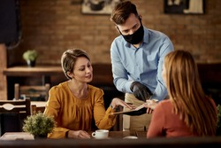 Young waiter serving customers and talking to them while wearing protective face mask in a pub.