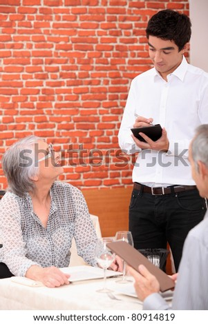 Young waiter taking an order in a restaurant - stock photo