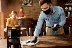 Young waiter wearing protective face mask while cleaning tables while working in a cafe.