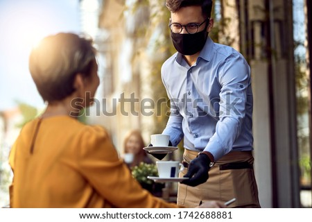 Young waiter wearing protective face mask while serving coffee to a customer in a cafe after reopening.
