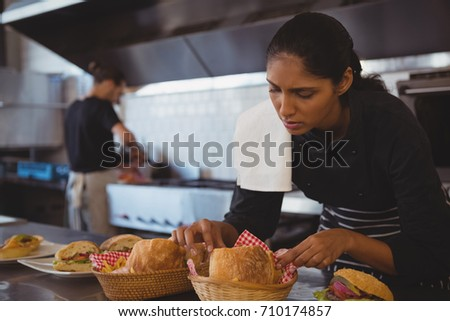 Young waitress arranging baskets with food at counter in cafe