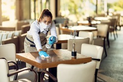Young waitress disinfecting tables while wearing protective face mask ad gloves due to coronavirus epidemic.