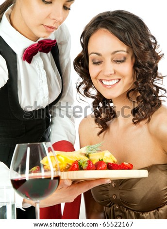 Young waitress offering fresh sliced fruits on wooden cutting board to beautiful female