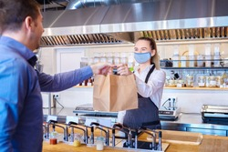 Young waitress waring protective face mask and apron serving customer at counter in small restaurant - Small business and entrepreneur concept with woman owner in eatery with takeaway service delivery