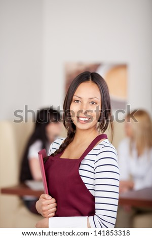 young waitress with red apron in cafe holding menu
