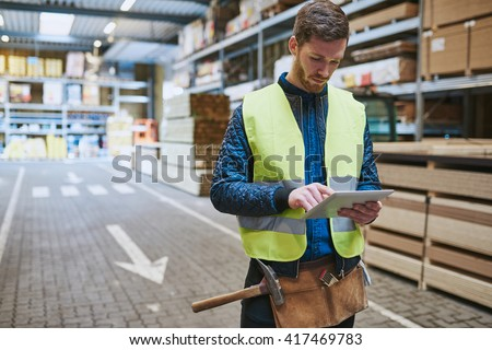 Young warehouse worker dealing in building supplies standing in a drive through consulting a handheld tablet computer