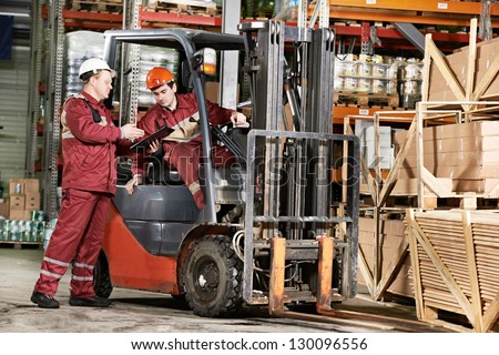 young warehouse workers in uniform in front of forklift stacker loader