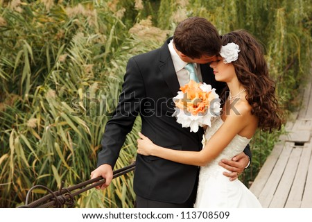 young wedding couple, beautiful bride with groom portrait on the bridge, summer nature outdoor #113708509