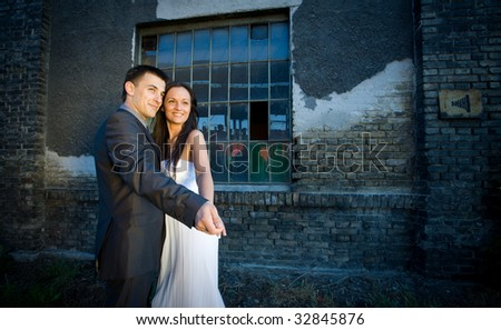 Young wedding couple dancing with old wall in background