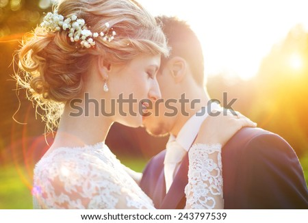 Young wedding couple enjoying romantic moments outside on a summer meadow #243797539
