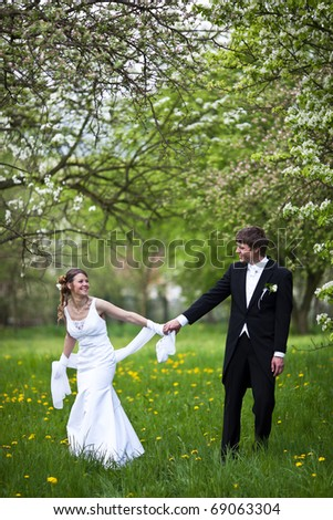 young wedding couple - freshly wed groom and bride posing outdoors, in a lovely blossoming orchard, on their wedding day - stock photo