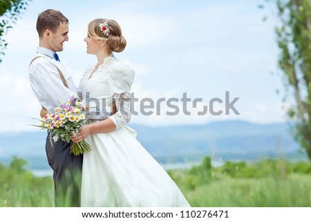 young wedding couple - freshly wed groom and bride posing outdoors on a lovely  day