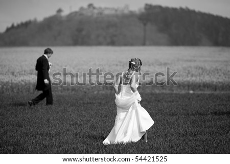 young wedding couple - freshly wed groom and bride posing outdoors on a lovely spring day