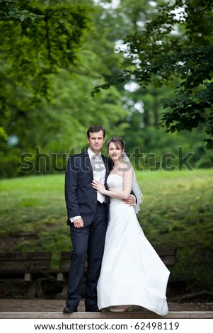 young wedding couple - freshly wed groom and bride posing outdoors on  their wedding day (color toned image)