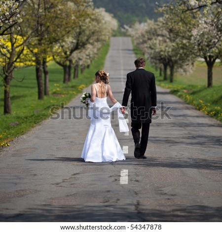 young wedding couple - freshly wed groom and bride walking on a road
