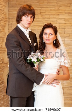 Young wedding couple indoors portrait.