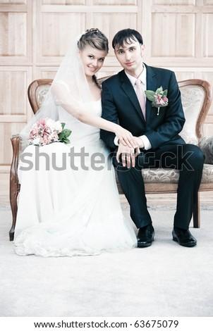 Young wedding couple interior portrait. Bright white colors.
