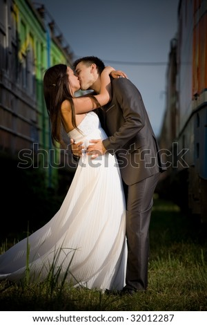Young wedding couple kissing between old trains