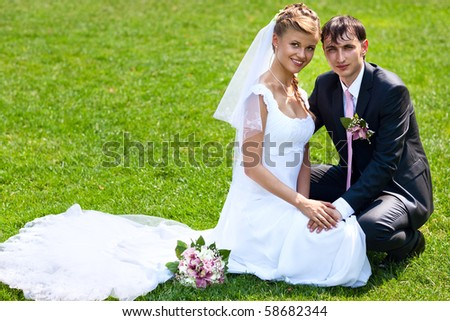 Young wedding couple on green grass