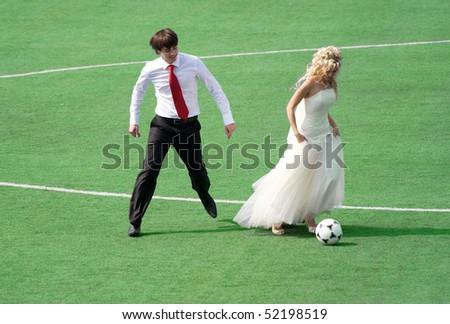 young wedding couple playing football on the green field