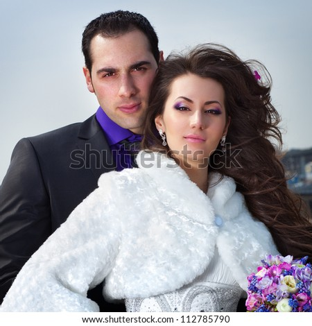Young wedding couple portrait on sky background.