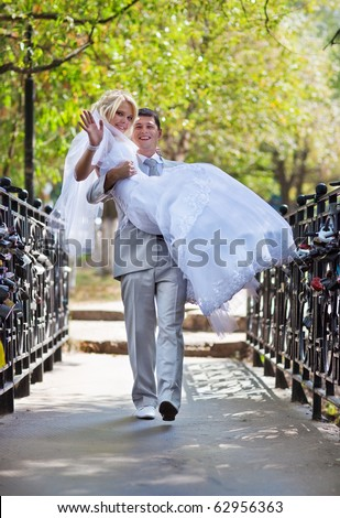 Young wedding couple walking on bridge.