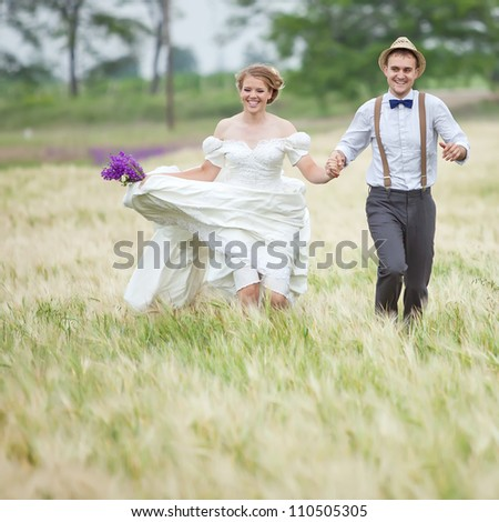 Young wedding couple walking on field.