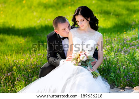 Young wedding couple walking on field. on the spring grass among yellow flowers dandelions