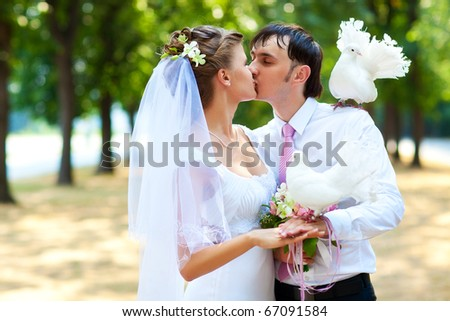 Young wedding couple with white pigeons.