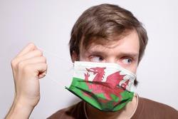 Young Welsh man wearing Wales face mask during coronavirus pandemic