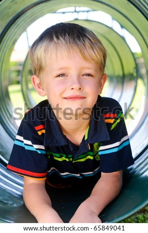 Young white boy sits in tunnel at the playground