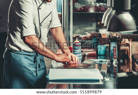 Young white chef in kitchen interior. Man marinating beef steak on a tray. Meat ready for the grill and serve. Only hands #551899879