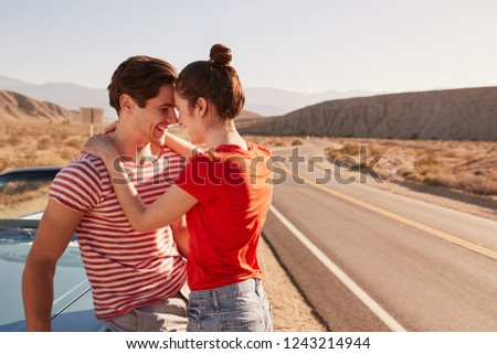Young white couple embracing by their car at the roadside