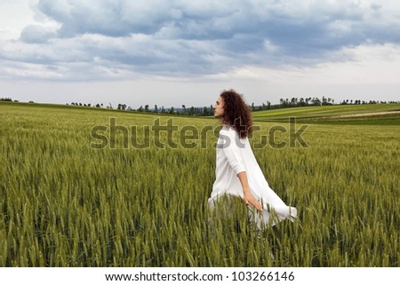 Young white dressed adult is striding through field of cereal plant and let flow his thoughts.