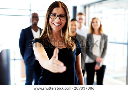 Young white female executive standing facing camera with hand stretched out and smiling