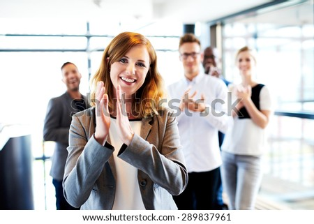 Young white female executive standing in front of colleagues clapping and smiling