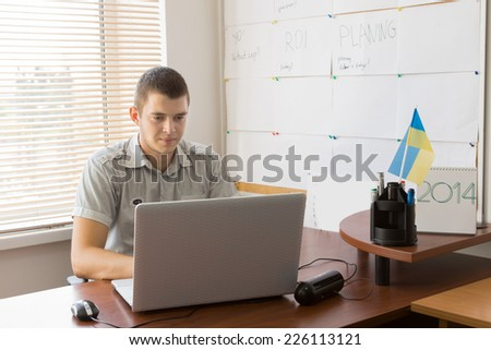 Young White Male Office Worker Busy Working with His Laptop Computer at His Table Area.