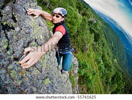 Young white man climbing a steep wall in mountain, rock-climb extreme sport, summer season. Horizontal orientation