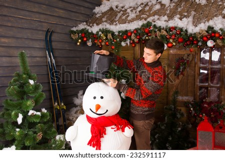 Stock Photo Young White Man in Winter Outfit Putting a Black Hat on Indoor Snowman, with Red Scarf, at Wooden House Surrounded by Christmas Ornaments.
