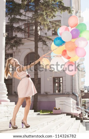 Young white woman holding colorful latex balloons, urban scene, outdoors
